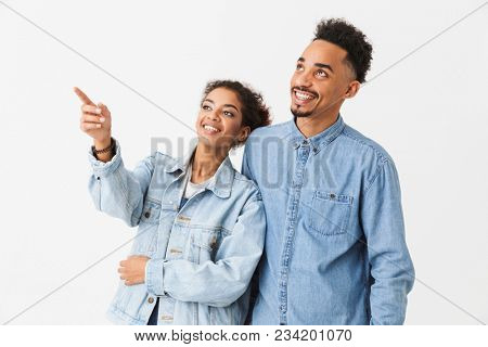 Happy african couple posing together and looking away while woman pointing away over grey background