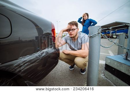 Man With Sad Look On Scratched Car. Woman With Sorry Look Near Dent Auto. Insurance Case.