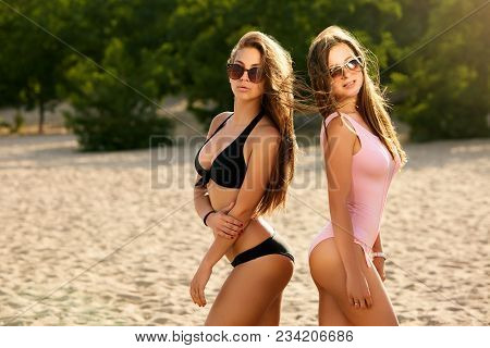 Two Suntanned Friends Sunbathing On The Beach And Having Fun. Girls Wearing Stylish Swimsuits And Su