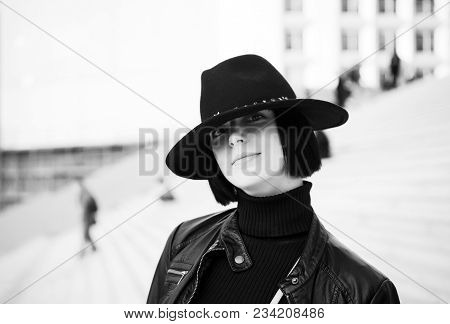 Woman In Black Hat And Jacket Pose On Stairs. Girl With Natural Makeup Face And Brunette Hair Outdoo