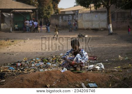 Bissau, Republic Of Guinea-bissau - January 29, 2018: Young Girl Collecting Waste In A Street Of The