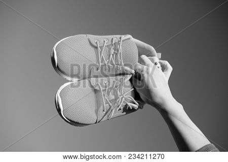 Sports Shoes Sneakers On Blue Sky Background. Sports In The Open Air. Woman Hand Holding Orange Snea