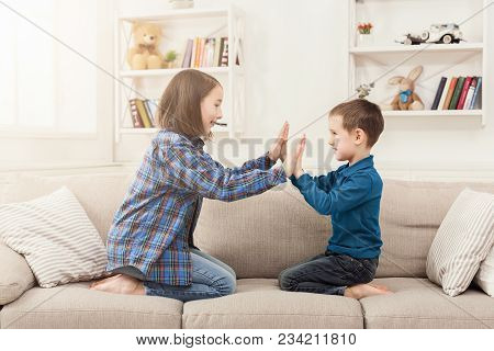 Brother And Sister Playing Clapping Hands Together At Home. Children Game, Joint Activities And Inte