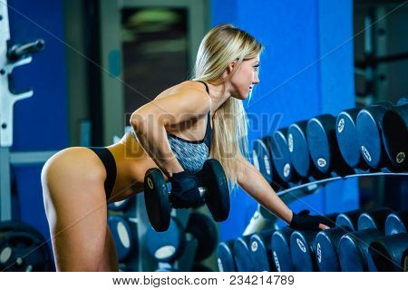 Young Sexy Woman Doing Exercises With Dumbbell In Gym. Classic Bodybuilding. Muscular Blonde Fitness
