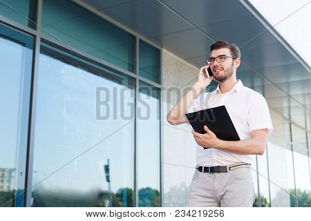 Attractive Smiling Businessman In Eyeglasses Is Holding Clipboard And Talking On Mobile Phone While