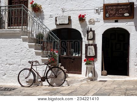 Ostuni, Italy - May 23, 2016: Old Bicycle In Front Of A White Plaster Wall With White Stairs, Red Ge
