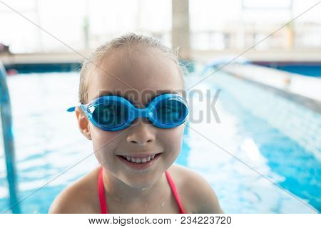 Cheerful Active Pretty Girl In Swimming Goggles Smiling At Camera In Modern Indoor Pool With Clean W
