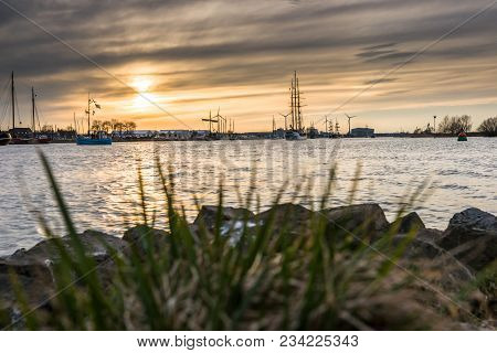 Silhouette Of Historic Sailboats On The Rivers Of The Netherlands. The Evening Falls In And In An At