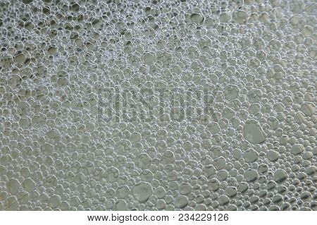 Small Bubbles Of Soap Foam On The Water