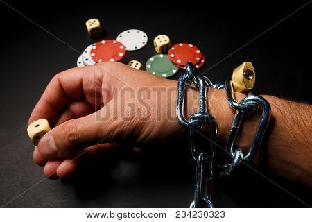 The Hand Is Chained Into The Chain As A Dependence On Gambling. On The Desk, Dice And Casino Chips.