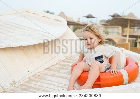 Child Sit In Ring Buoy On Sunny Day. Little Boy With Lifebuoy On Tropical Beach. Kid With Blond Hair
