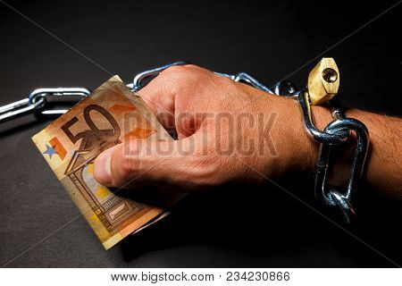 Hand In The Chain With Cash Euro As A Symbol Of Dependence On Advertising And Marketing. Photography