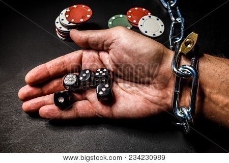 The Hand Is Chained To The Chain As A Dependence On Gambling. The Photo Can Illustrate Materials Abo