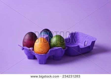 Colorful Easter eggs in purple egg box. Decorated Easter eggs  on purple background.