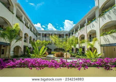 Cancun, Mexico - March 18, 2018: A Courtyard Filled With Flowers And Palm Trees At The Grand At Moon