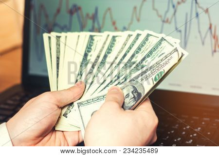 Dollars In Hands On Computer Background, The Concept Of Buying On The Internet, Investment, Success,