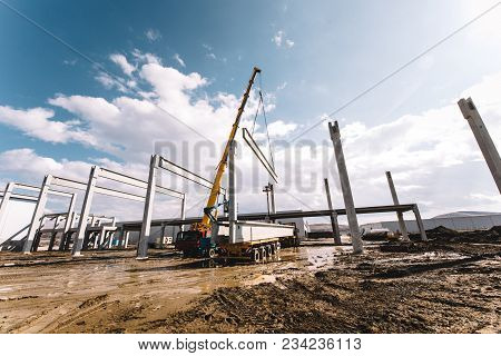 Details Of Construction Site With Crane Lifting Prefabricated Concrete Framework, Unloading And Carg
