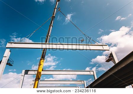 Industrial Construction Site With Tower Crane Working With Prefabricated Beams And Pillars