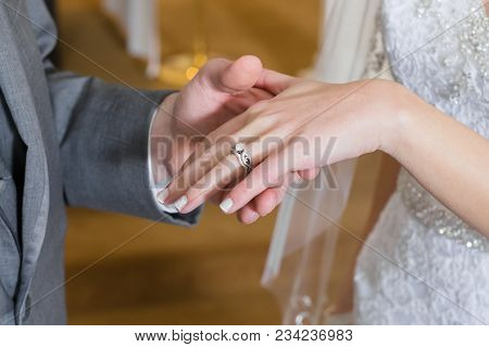 Close Up Of Bride And Groom Hands. Groom Has Just Placed Bridal Wedding Band And Engagement Ring On
