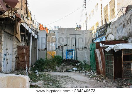 Blocked road exit in the city of Hebron to separate a jewish settlement from a palestinian street. With former shops beeing welded tight poster