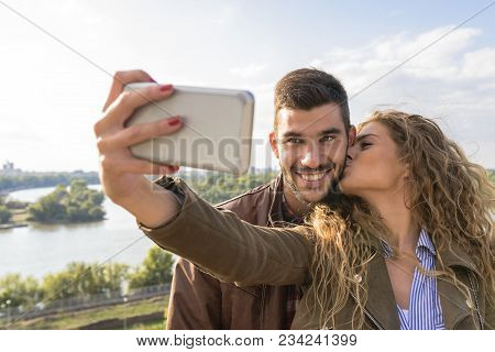 Beautiful Young Woman Taking Selfie In The Nature While Kissing Her Handsome Boyfriend