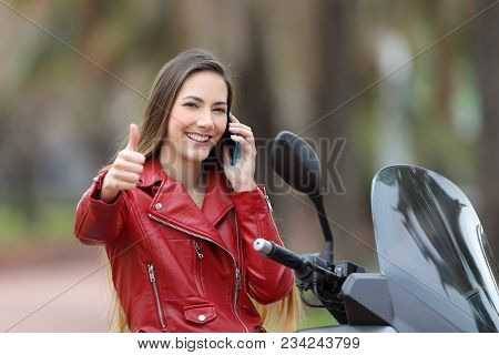 Happy Biker Sitting On A Motorbike With Thumbs Up Calling On Phone On The Street