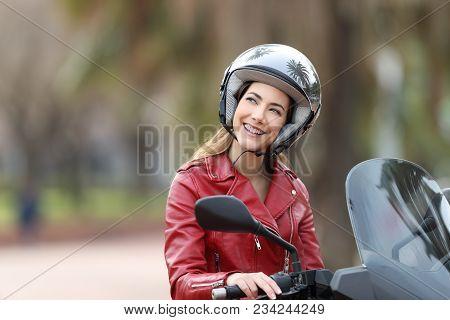 Happy Biker Wearing Helmet Sitting On A Motorbike Dreaming Looking Above On The Street