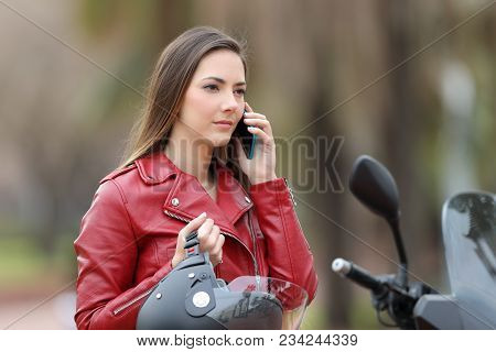 Portrait Of A Serious Biker Waiting During A Phone Call To Insurance On A Motorbike On The Street