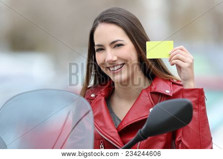 Happy Biker Showing A Credit Card Or Driving License On A Motorbike On The Street