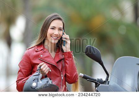 Happy Biker Calling On Smart Phone On A Motorbike On The Street