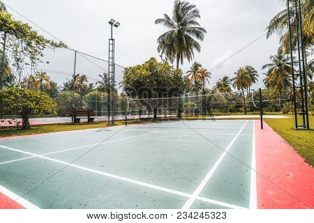 Side Wide-angle View Of The Badminton Court On A Summer Day: Red And Green Field With Marking On The