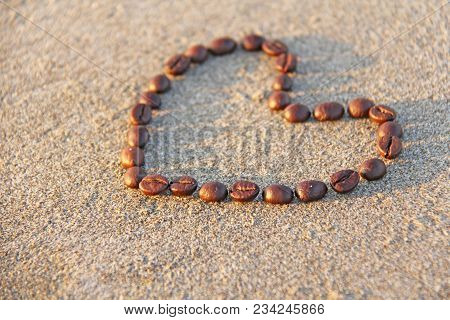 Heart Of Coffee. Grains Of Coffee Are Laid Out On Sand In The Form Of Heart. Love Of Coffee. Design
