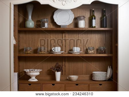 Kitchen cupboard with nice rustic dinnerware. Wooden kitchen cabinet cupboard with many white dishes, plates, cups, jars and wine bottles on shelves poster
