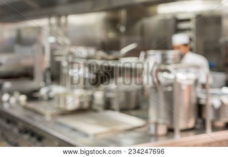 Defocused Chef Preparing Food In Commercial Stainless Steel Kitchen In Restaurant