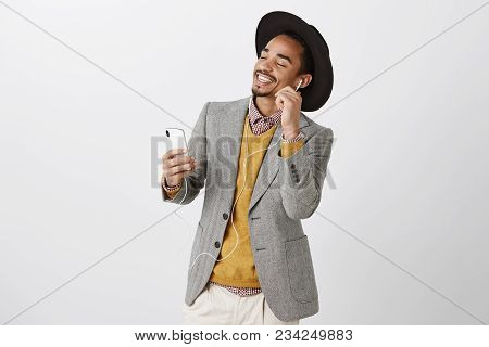 Music Relieves From Stress. Satisfied Relaxed Attractive Guy In Classy Suit And Trendy Hat, Dancing