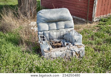 An old blue recliner chair has been left outside to gradually decompose in the weeds of an overgrown yard.
