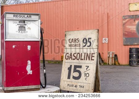 Old Car Gas Station, Advertising For Cheap Gasoline, Metal Barrel In Summer Day