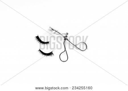 Curled And Thick Eyelashes. False Eyelashes And Eyelash Curler On White Background Top View.