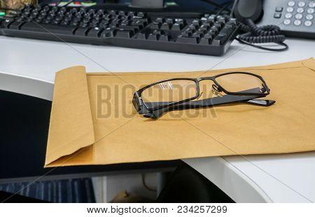 Men Modern Eyeglasses On Brown Confidential Envelope On Office Desk