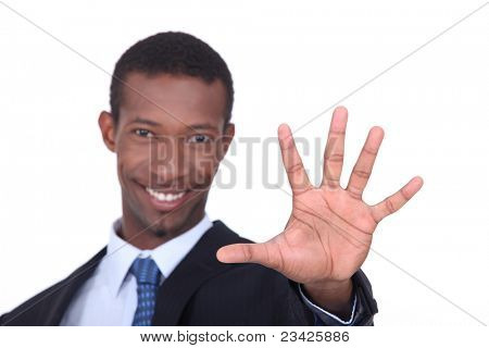 Studio shot of a businessman with the palm of his hand outstretched in front of him