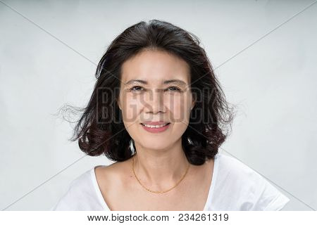 Portrait Of Beautiful Mature Asian Woman With Curly Hair Style Smiling With Joyful And Charming On W