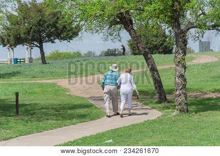 Rear View Of Happy Senior Couple Walking In The Bluebonnet Park