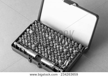 A Set Of Bits For A Screwdriver Of Different Shapes In The Box On A Gray Background Close-up. Tool F