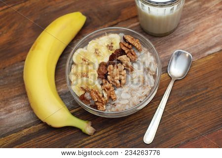 Top View Of A Granola Bowl, Muesli With Oats, Nuts And Dried Fruit On Wooden Table. Healthy Breakfas