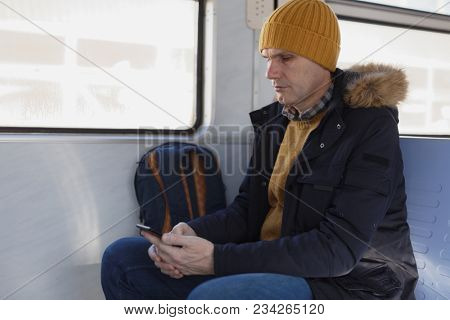 Man in winter clothing with smartphone in a commuter train
