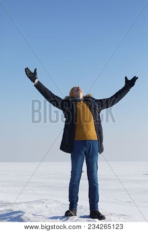 Man in winter clothes with hands up on the ice of Gulf of Finland