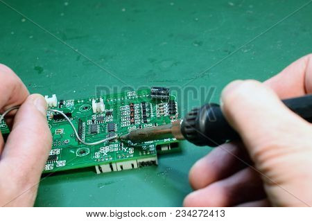 Man Using Soldering Iron To Repair Circuit Board On Green Surface. Space For Text.