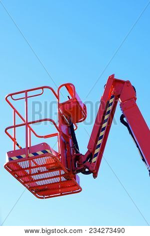Red Cherry Picker Work Platform Against Clear Blue Sky. Vertical Image With Space For Text.
