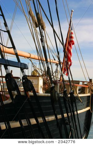 An American Flag Hanging From A Tall Ship