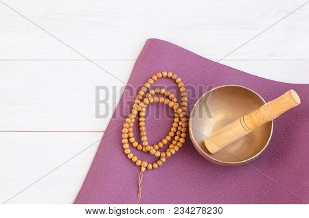 Yoga Mat, Wooden Mala Beads And A Tibetan Bowl On Wooden Background. Essential Accessories For Pract